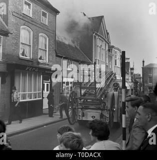 1964, Silver Street, Aylesbury,  the fire brigade in attendance, showing fire engine of the day with ladder attached as a  small old shop, 'The Town Stationers' has smoke coming out of its roof. - Stock Image