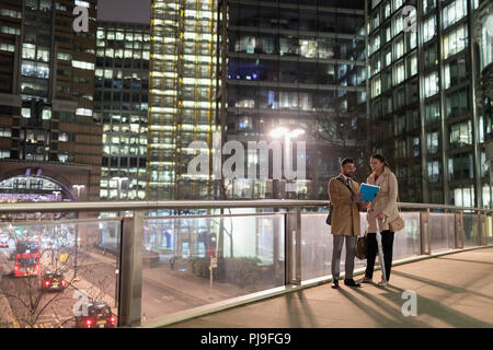 Business people discussing paperwork on urban pedestrian bridge at night - Stock Image