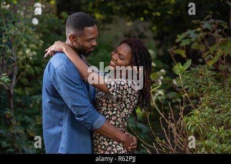 A couple hugging in a garden - Stock Image
