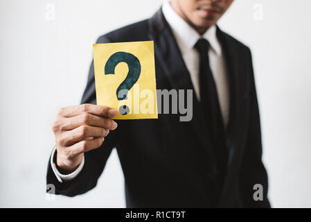 Young businessman holding a card with QUESTION MARK. Concept of Business Strategy, solution and problem - Stock Image
