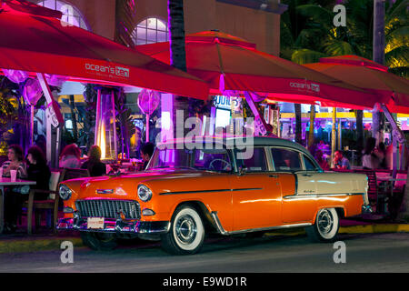 Orange and white two-tone 1955 Chevy Chevrolet Bel Air 4-door sedan parked in front of Ocean's Ten on Deco Drive, - Stock Image