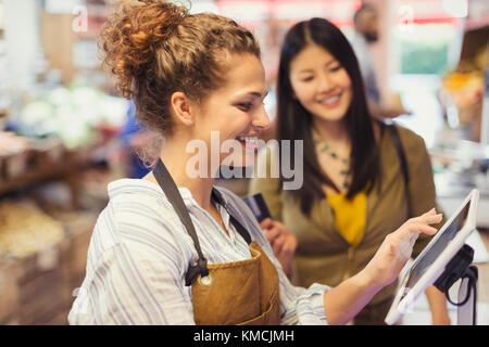 Female cashier helping customer at touch screen cash register in grocery store - Stock Image