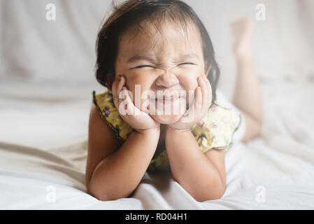 cute little asian girl toddler smiling on bed. concept of happiness, childhood and lifestyle - Stock Image