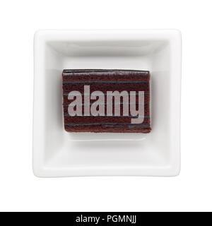 Slice of chocolate cake in a square bowl isolated on white background - Stock Image