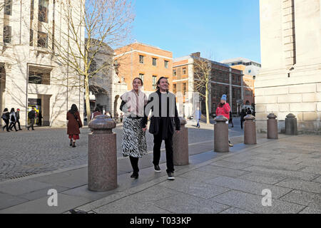 A smiling tourist couple holding hands stroll near St Pauls Cathedral exterior in the City of London England UK    KATHY DEWITT - Stock Image