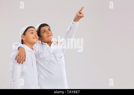 Young Muslim boys wearing cap looking away, smiling and pointing - Stock Image