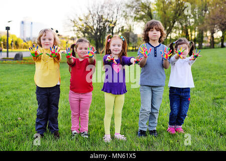 a group of small children with hands dirty in color paint play in the park. - Stock Image