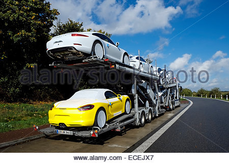 Porsche cars on auto carrier parked at a rest stop in Lower Saxony, Germany - Stock Image