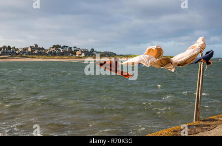 North Berwick, East Lothian, Scotland, United Kingdom. 7th December 2018. UK Weather: A bright sunny but very windy day in the seaside town with gusts of wind of up to 50-60mph forecast. Washing hanging on a line blows in the wind at the harbour - Stock Image