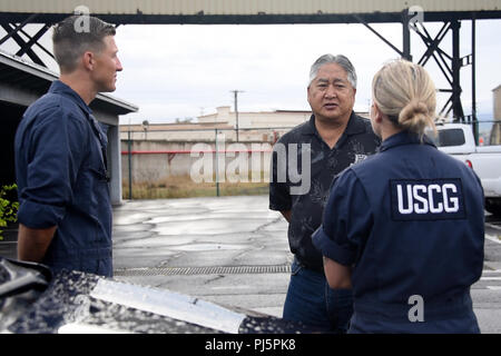 Petty Officer 2nd Class Kim Fennick and Petty Officer 2nd Class Matthew Vincent speak with Hawaii Department of Transportation Kahului Harbor District Manager Duane Kim during a post-hurricane port assessment of Kahului Harbor in Kahului, Hawaii, Aug. 25, 2018. Coast Guard assessment teams are working to ensure ports are safe to reopen following Hurricane Lane. Coast Guard photo by Petty Officer 1st Class Patrick Kelley. - Stock Image