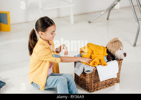 child sitting and putting clothes to basket at home - Stock Image