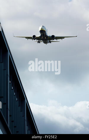 Jet flying over buildings - Stock Image