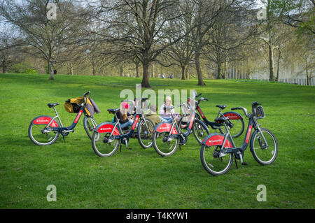 A group of young people in St. James Park with Santander Boris Bikes - Stock Image