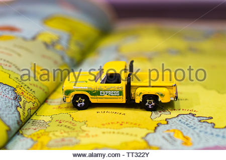 Mattel Hot Wheels toy yellow Chrysler pick up truck on a European map from a educational atlas book on circa June 2019 in Poznan, Poland. - Stock Image