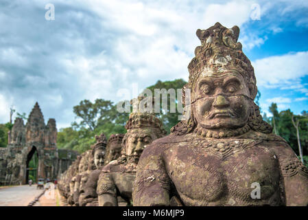 Statues of 54 'devas'  lining the causeway to the South gate of Angkor Thom in Cambodia. - Stock Image