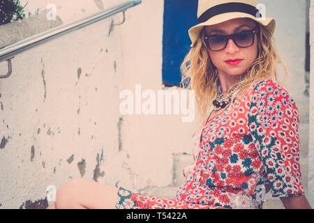 Beautiful young caucasian woman in fashion style coloured dress pose and relax - summer style with sunglasses and hat for trendy people outdoor - Stock Image