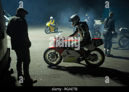 Motorcycle riders prepare in the cold to ride through the dinner guests at Goodwood House to mark the start of the annual Members Meeting - Stock Image