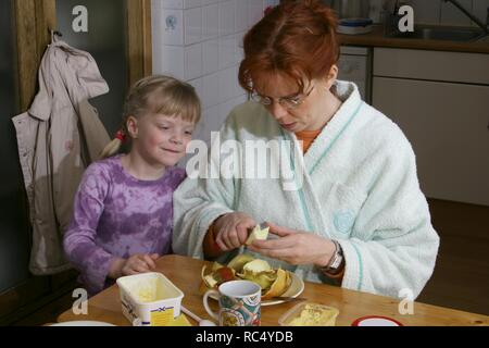 Over 40 mother in housecoat peeling an apple for her girl child at the breakfast table at home - Stock Image