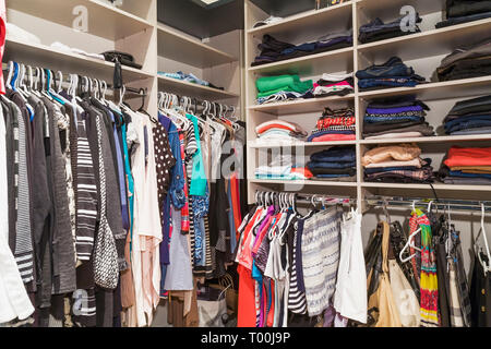 Walk-in closet with women's clothes on hangers and on shelves next to master bedroom inside a luxurious contemporary bungalow style home - Stock Image
