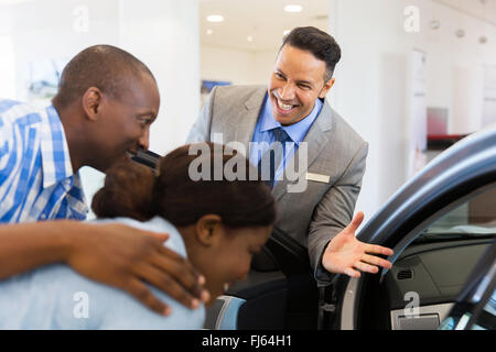 friendly vehicle dealer selling new car to young couple in showroom - Stock Image