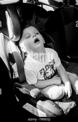 Two year old boy sleeping in the car, Medstead, Alton, Hampshire, England, United Kingdom. - Stock Image