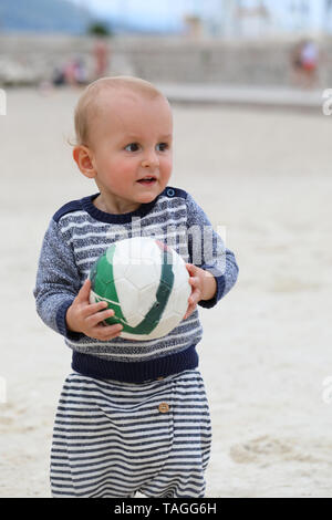 Adorable Blond Baby Boy is Holding a Soccer Ball on Sand on Sea Beach - Stock Image