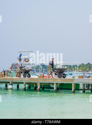 Workers remove depleted SCUBA tanks from a tourist dive boat at West Bay Beach Roatan Honduras. - Stock Image