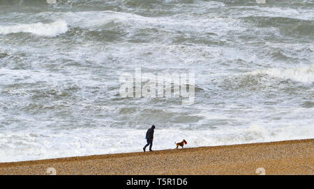 Brighton, UK. 27th Apr, 2019. A lone dog walker on Brighton beach as Storm Hannah hits Britain this morning with strong winds forecast to affect parts of the country Credit: Simon Dack/Alamy Live News - Stock Image