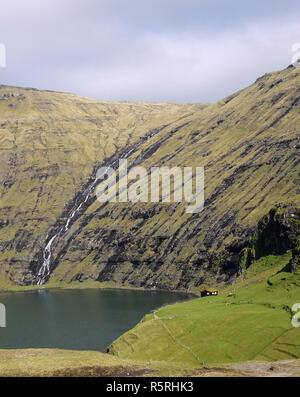 Waterfall at Saksun with tiny red tin roof house on the side of the sea inlet in the Faroe Islands - Stock Image