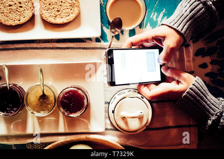 Breakfast morning and chat messages with mobile phone - people working with technology or addicted to internet - home or hotel travel lifestyle for mo - Stock Image