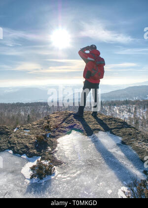 Hiker relaxing on top of hill and enjoying on sunny day. Tourist  trekking along a hill - Stock Image