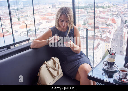 Young woman using gadget in rooftop cafe - Stock Image