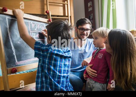 Older brother is writing on a blackboard, parents and the little brother are watching, Munich, Germany - Stock Image