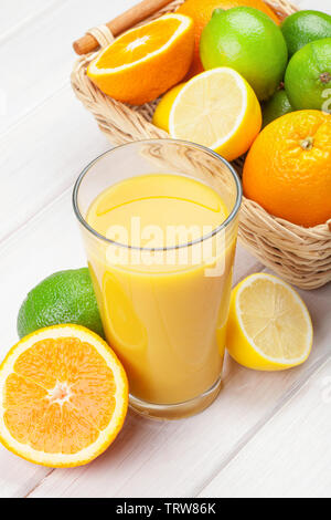 Orange juice and citrus fruits on white wooden table - Stock Image