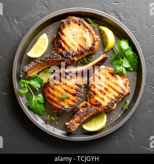 Close up of grilled pork steaks on plate over black stone background. Top view, flat lay - Stock Image