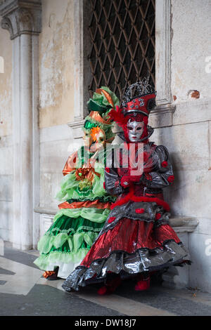 Venice, Italy. 25th Feb, 2014. Two costumed ladies sit outside of the Doge's palace. Venice Carnivale - Tuesday 25th February. Credit:  MeonStock/Alamy Live News - Stock Image