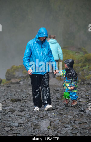 Father and son walking on stone footpath after a soaking near Skogafoss waterfall, Iceland - Stock Image