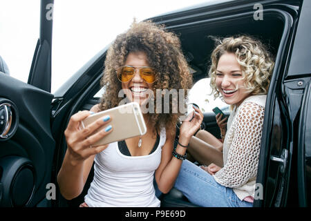 Portrait of two smiling young women with blond and brown curly hair sitting in car, taking selfie with mobile phone. - Stock Image