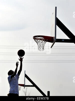 Jayqwan Wilkins of New Haven enjoys the spring-like weather as he played basketball with friends at Criscoulo Park - Stock Image
