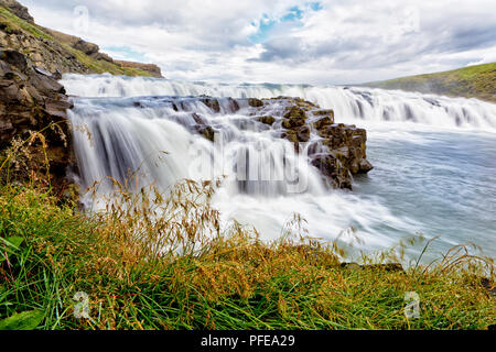 GULLFOSS, ICELAND. 3RD AUGUST 2016: Long exposure of first set of waterfalls in Gullfoss with green reed in the foreground. - Stock Image