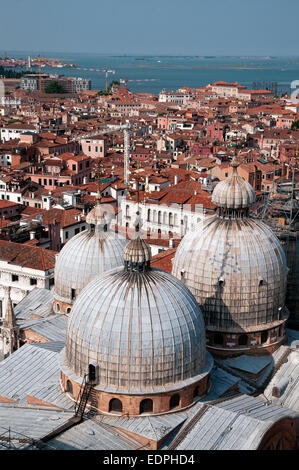 Domes of Basilica di San Marco St Marks Cathedral seen from top of St Marks Bell Tower Venice Italy with sea beyond - Stock Image