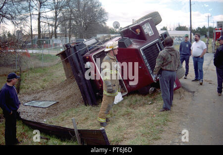 Firefighters examine an overturned tractor trailer in Largo, Maryland - Stock Image