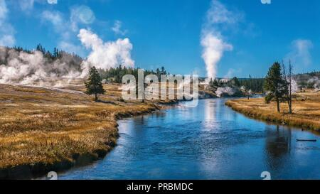 View of the Firehole River flowing through Yellowstone's Upper Geyser Basin, part of the most active geyser field in the world. Old Faithful can be se - Stock Image