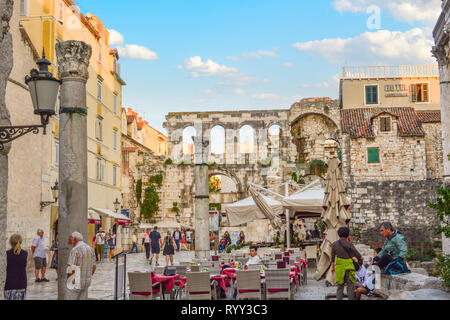 Tourists pass bay a cafe at dusk in the Diocletian's Palace section of the ancient city of Split Croatia with the Silver Gate behind. - Stock Image