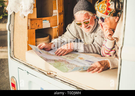 Old senior couple enjoy the travel vacation planning lay down inside a vintage van - happy lifestyle for retired people enjoying life - together forev - Stock Image
