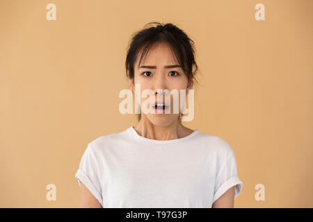 Portrait of confused asian woman wearing basic t-shirt wondering and looking at camera with open mouth isolated over beige background in studio - Stock Image