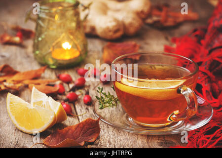 autumn tea with ginger, lemon, thyme, wild rose on the old wooden background (Toning) - Stock Image