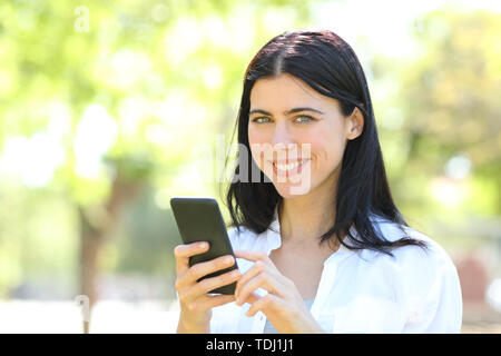 Happy adult woman holding smart phone looking at camera in a park - Stock Image