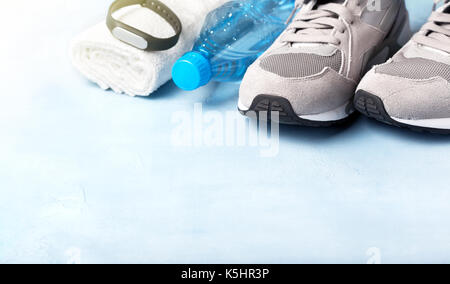 gray sneakers, water bottle, white towel and fitness bracelet on a blue background - Stock Image
