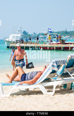 Tourist relaxes in the warm sun on West bay beach in Roatan Honduras. - Stock Image